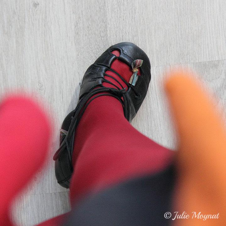 En soft shoes de danses irlandaises : des chaussons en cuir noir qui ne recouvre pas le dessus du pied et dont le laçage croisé laisse bien voir le pied, ici en collants rouges